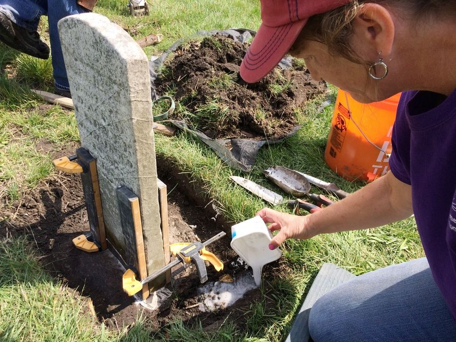 Christine Hillmann, a cemetery preservationist, works on righting one of the gravestones at Fort Hill Cemetery, established in 1844 near Round Lake.