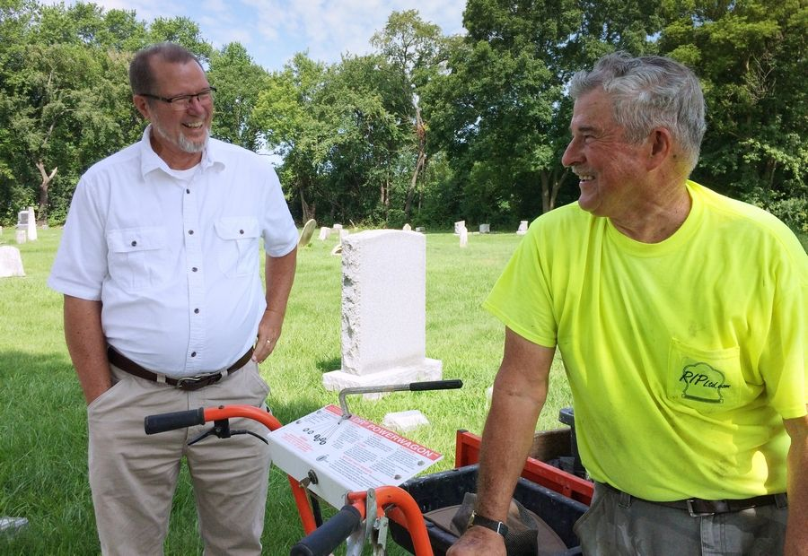 Vern Paddock, left, has written genealogies for more than 330 individuals buried in the Fort Hill Cemetery near Round Lake and created a website to share the information. Paddock talks with John Heider, a cemetery preservationist, who has been hired to repair and reset grave markers.